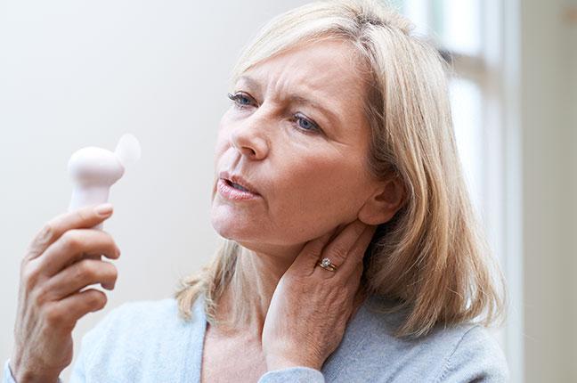 mulher com calor por causa da menopausa