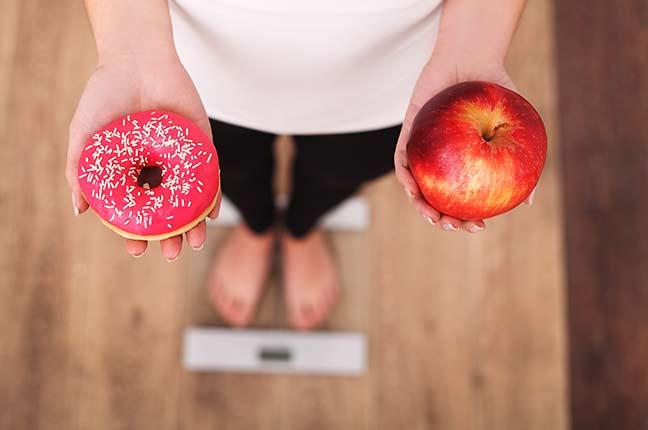 mulher em cima de balança fazendo dieta