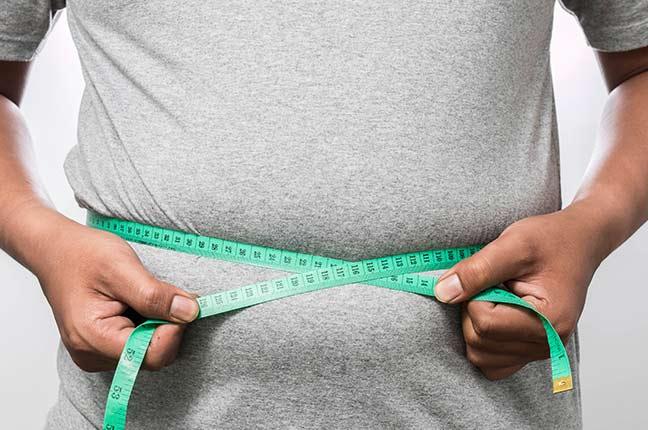 homem obeso com fita métrica